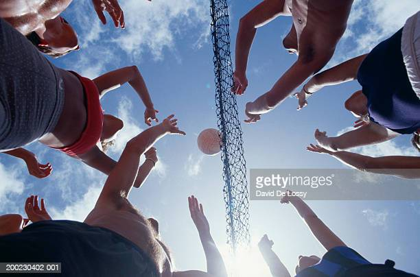 Young people playing volleyball, view from below