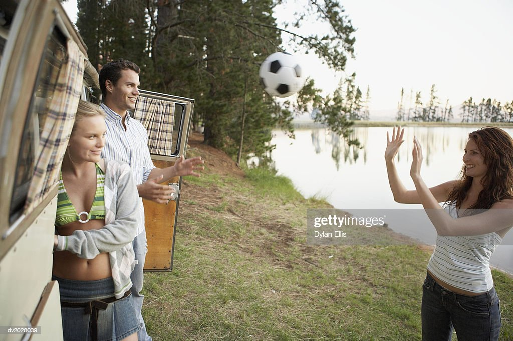 Young People Playing With a Ball by a Lake : Stock Photo