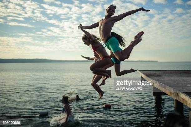 TOPSHOT Young people plunge during the traditional New Year's jump into the Adriatic sea in Portoroz on January 1 2016 / AFP / JURE MAKOVEC