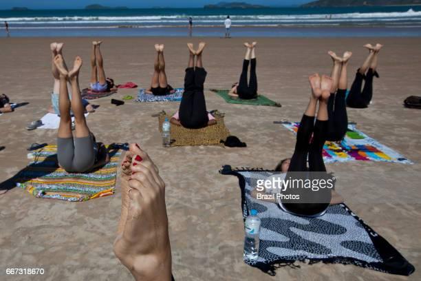 Young people practicing yoga at Geriba beach Armacao de Buzios Rio de  Janeiro State Brazil physical 6dbd128ff7