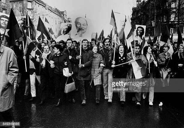 young people protest and carry flags and posters with photographs of Ho Chi Minh Rosa Luxemburg und Che Guevara
