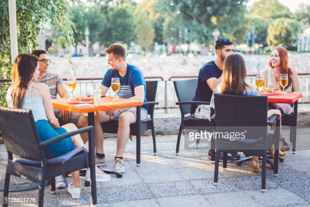 young people relaxing in patio section - patio stock pictures, royalty-free photos & images