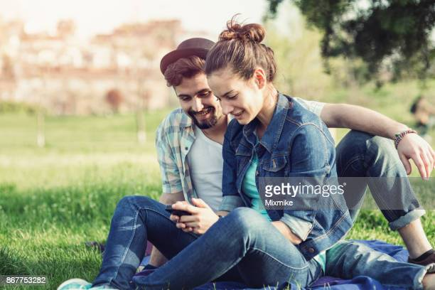 Young people relaxing in the park and surfing the net