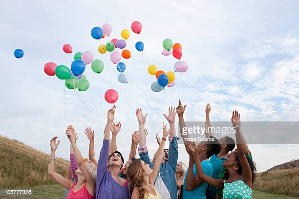 young people releasing balloons - releasing stock photos and pictures