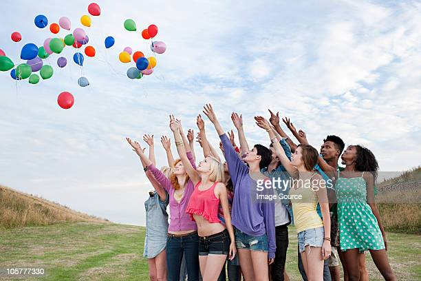 young people releasing balloons - releasing stock pictures, royalty-free photos & images