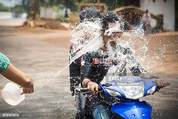Young people riding a motorbike being splashed by water during Thingyan Water Festival, Myanmar's traditional New Year Festival, in April 2016