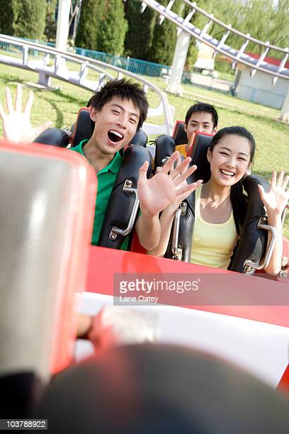 Young people riding a rollercoaster