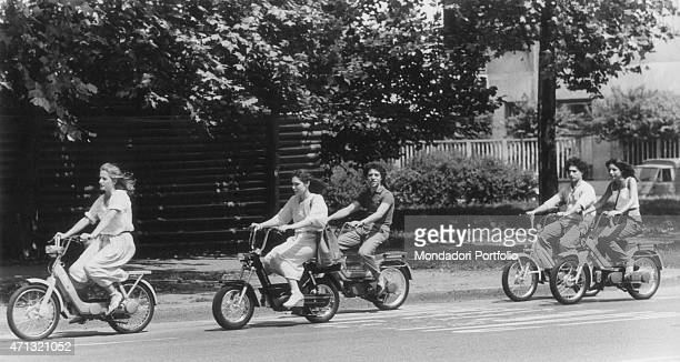 Young people riding scooters 1970s