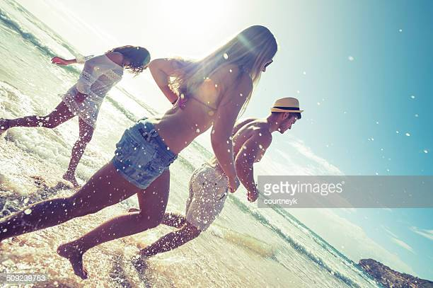 Young people running on the beach in the sun