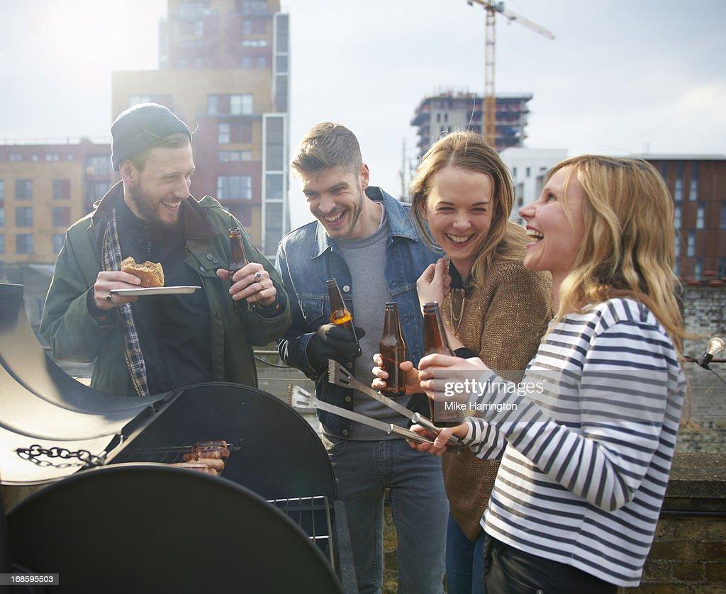 Young people sharing beers around barbecue. : Bildbanksbilder