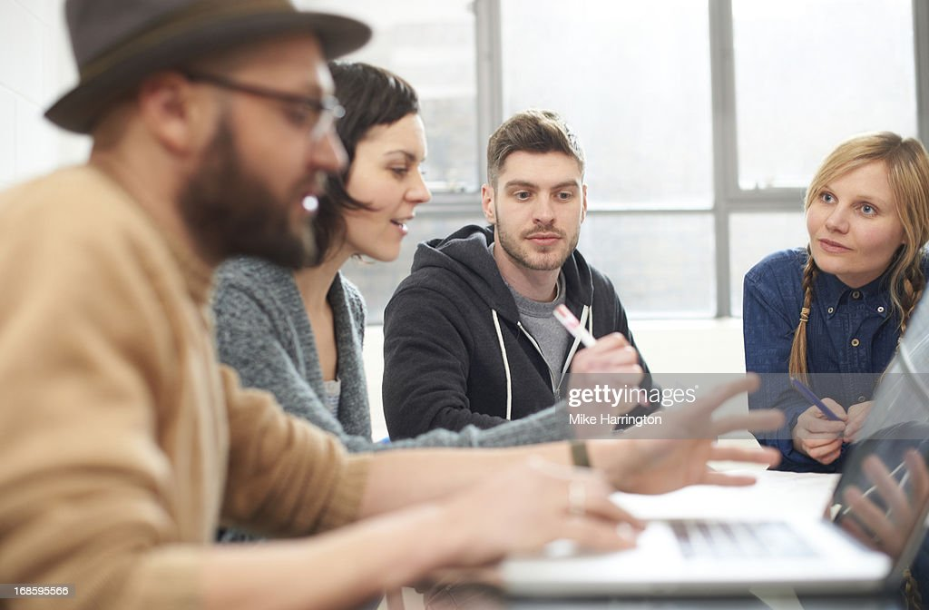 Young people sharing ideas during meeting. : Stock Photo