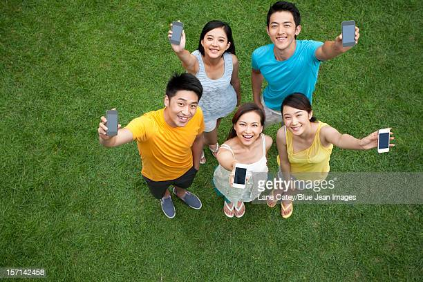 young people showing mobile phones on meadow