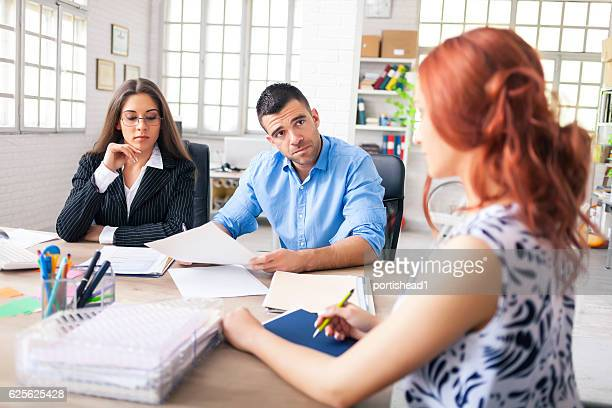 Young people signing papers in modern office
