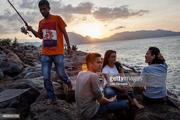 Young people sit as they enjoy their time at Ulee Lheu beach on December 12 2014 in Banda Aceh Indonesia Aceh is the only province to implement...