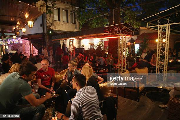 Young people sit at an outdoor cafe smoking shishas on the eve of the centenary of the assassination of Austrian Archduke Franz Ferdinand and his...