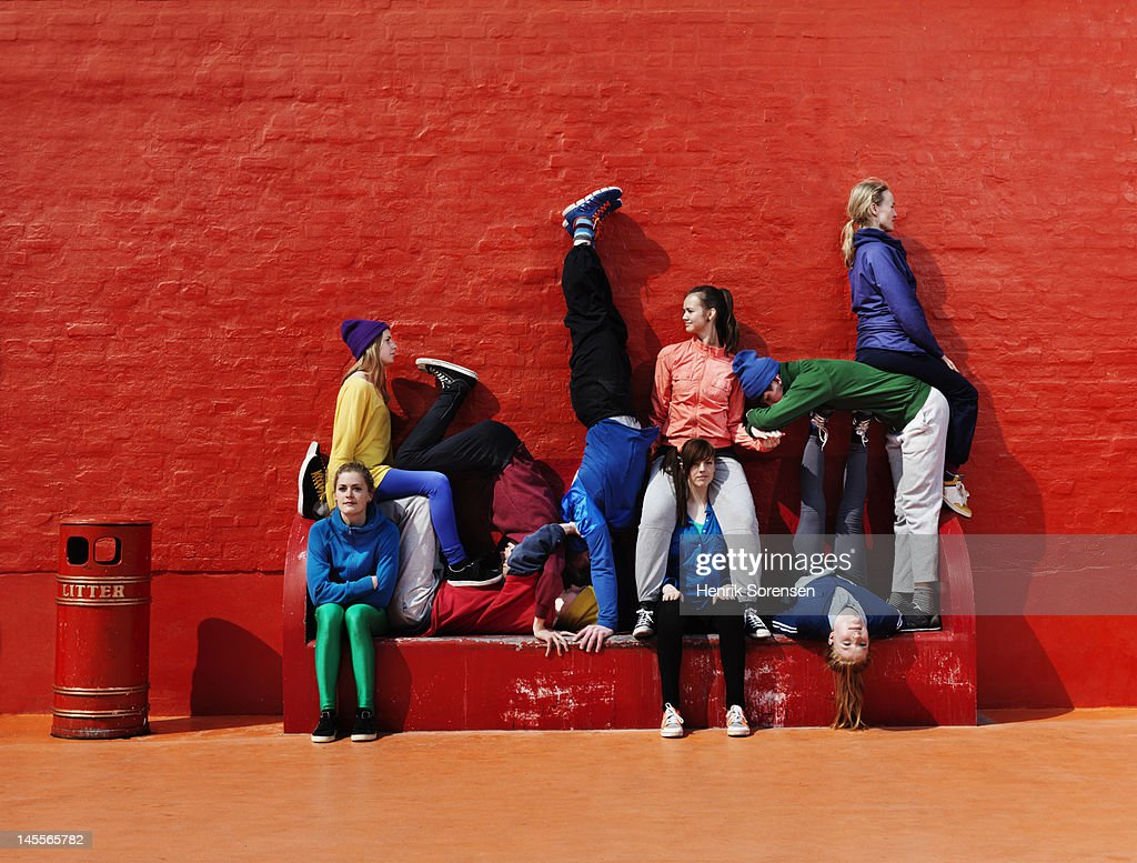 Young people sitting and stading on a bench : Stockfoto