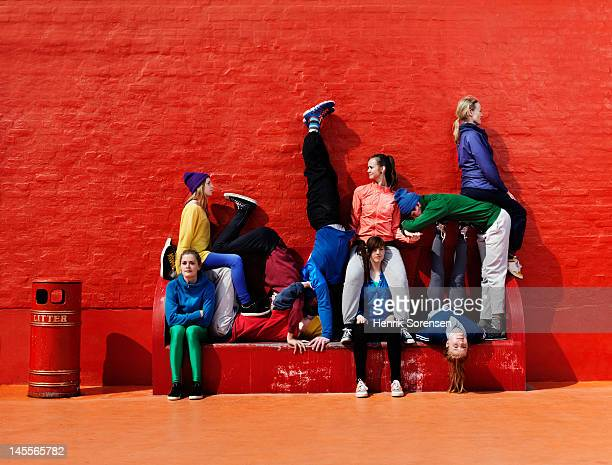 young people sitting and stading on a bench - street style stock pictures, royalty-free photos & images