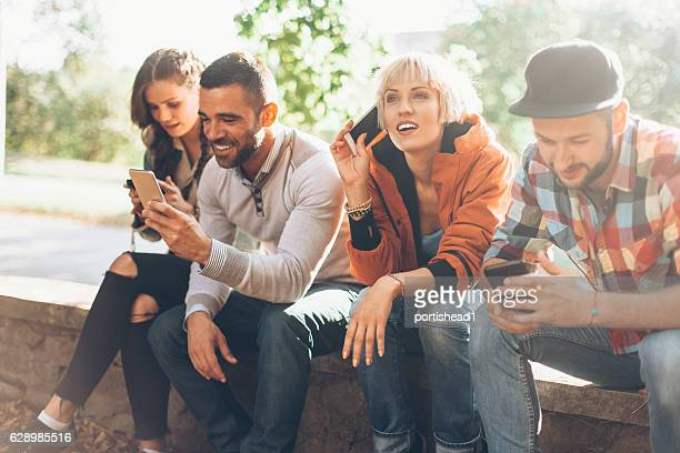 Young people sitting and using mobile phones
