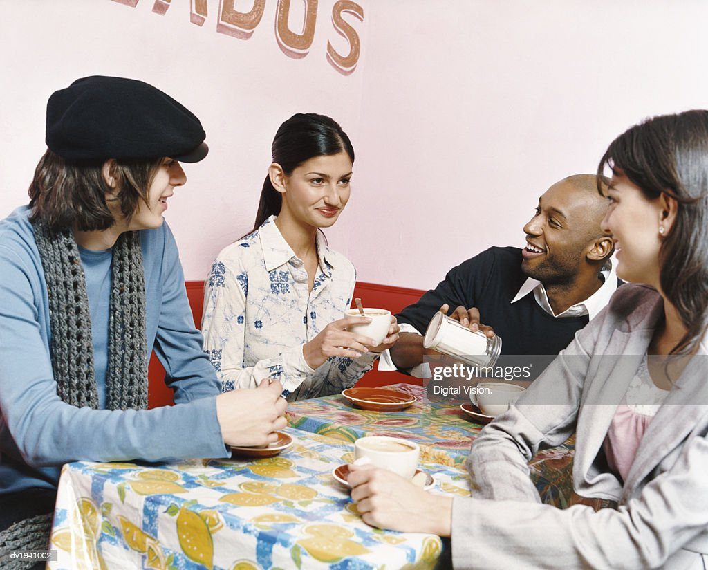 Young People Sitting at a table in a Cafe : Stock Photo