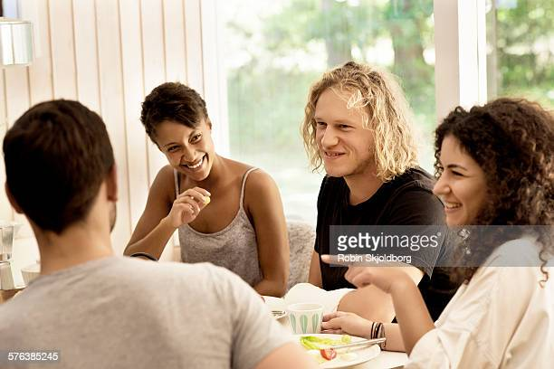 young people sitting at table talking - robin skjoldborg stock pictures, royalty-free photos & images