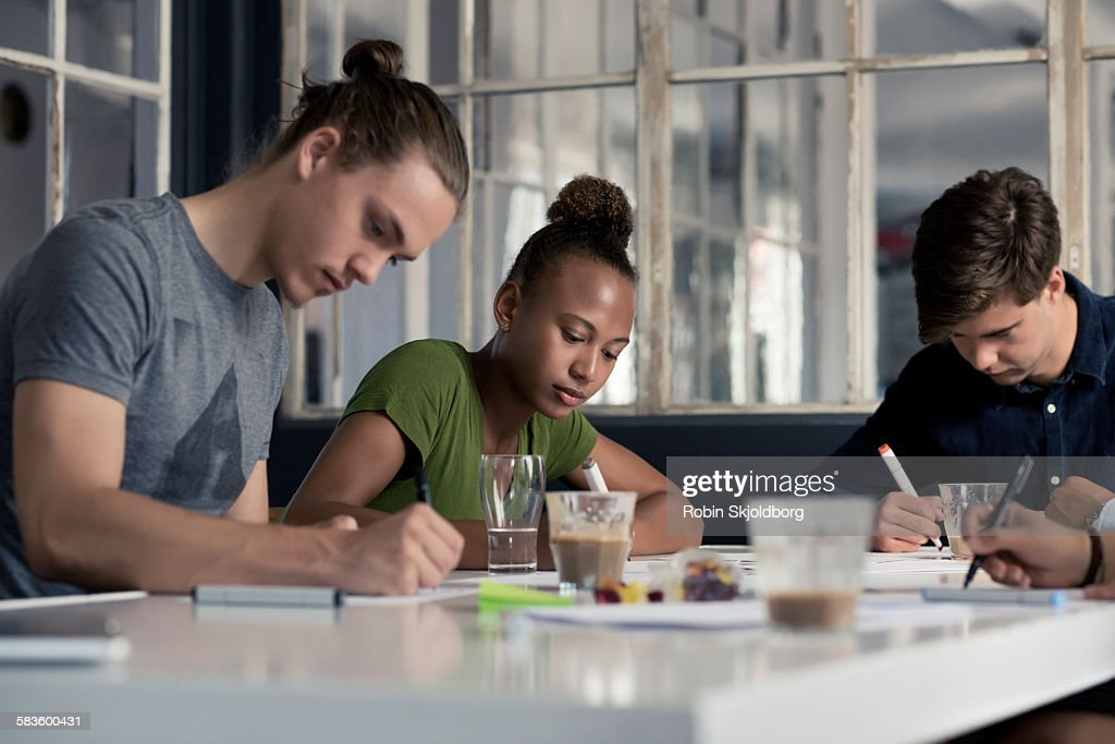 Young people sitting at table writing : Stock Photo