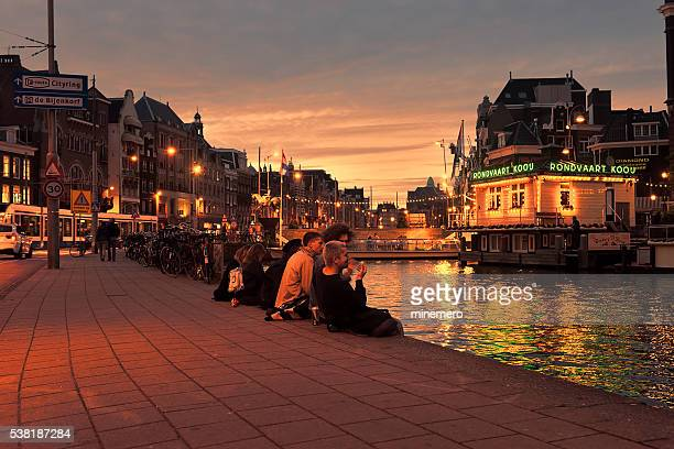 Young people sitting canal at night