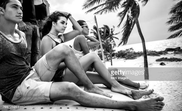 young people sitting on a beach and looking out to sea. - mexico black and white stock pictures, royalty-free photos & images