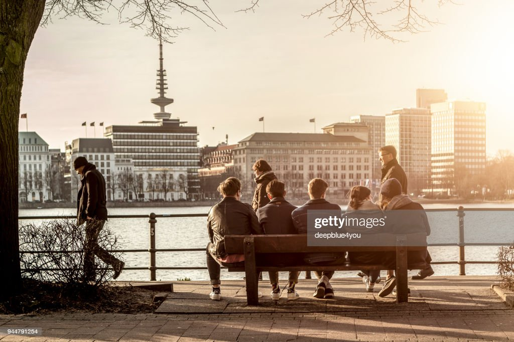 Young people sitting on a bench in the sunshine and looking at the Hamburger Alster lake : Stock Photo