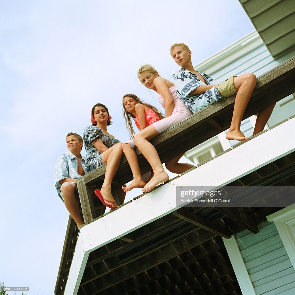 Young people sitting on balcony, low angle view : Stockfoto