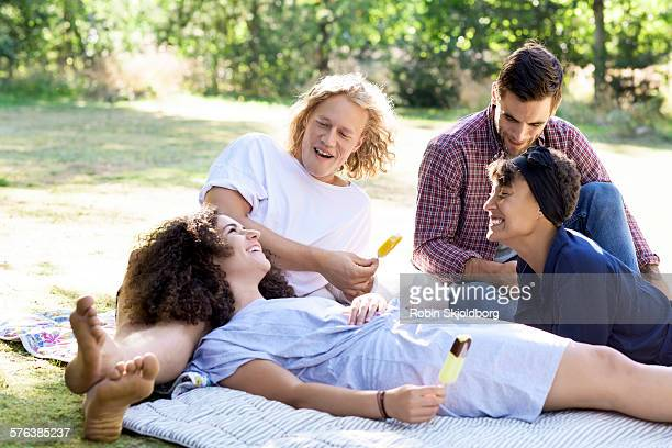 young people sitting on lawn with ice creams - robin skjoldborg stock pictures, royalty-free photos & images