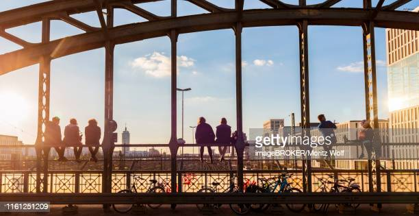 young people sitting on the balustrade of the hackerbruecke bridge over the railway tracks and looking into the distance, back light, munich, upper bavaria, bavaria, germany - münchen stock-fotos und bilder