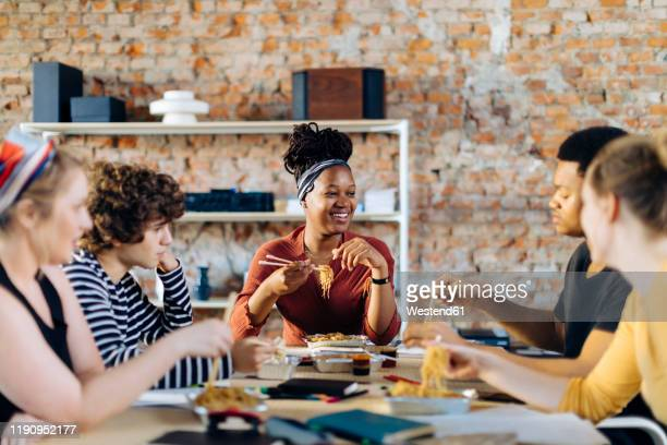 young people sitting together at table having lunch break - founder stock pictures, royalty-free photos & images