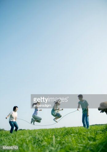 Young People Skipping On Grass Stock Photo - Getty Images