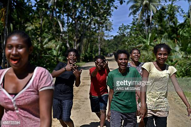 Young people smile and gesture while walking on a road near the village of Tora in the jungle of Papua New Guinea on September 9 2014 AFP PHOTO /...