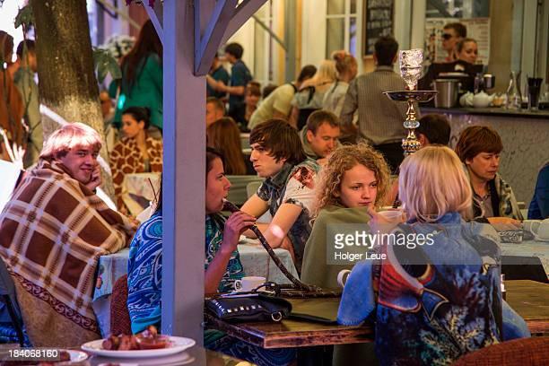 Young people smoke Sheesha pipes at cafe and bar