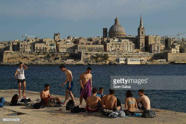 Young people speaking Italian relax on the waterfront as Valletta, including the dome of the Basilica of Our Lady of Mount Carmel, stands behind on...