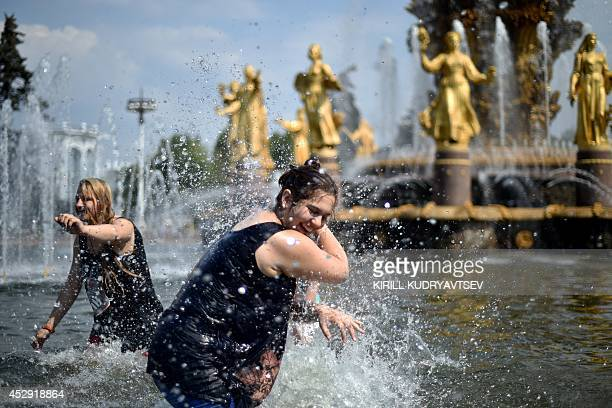 Young people splash water at each other while standing in the pool of famous Druzhba narodov fountain at the VDNKh a public park and exhibition space...