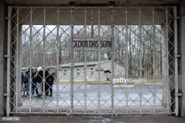 Young people stand in front of the former main entrance to the Buchenwald concentration camp on January 26 2018 near Weimar Germany International...