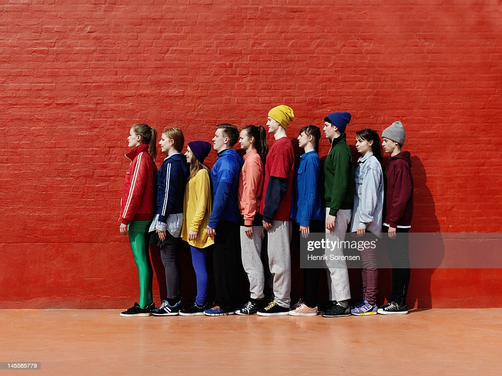 Young people standing against each other : Stock Photo