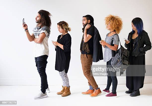 young people standing in line using smartphones - lining up stock pictures, royalty-free photos & images