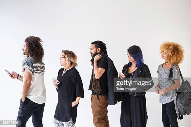Young people standing in line using smartphones