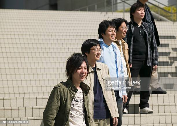 Young people standing in row on stairs