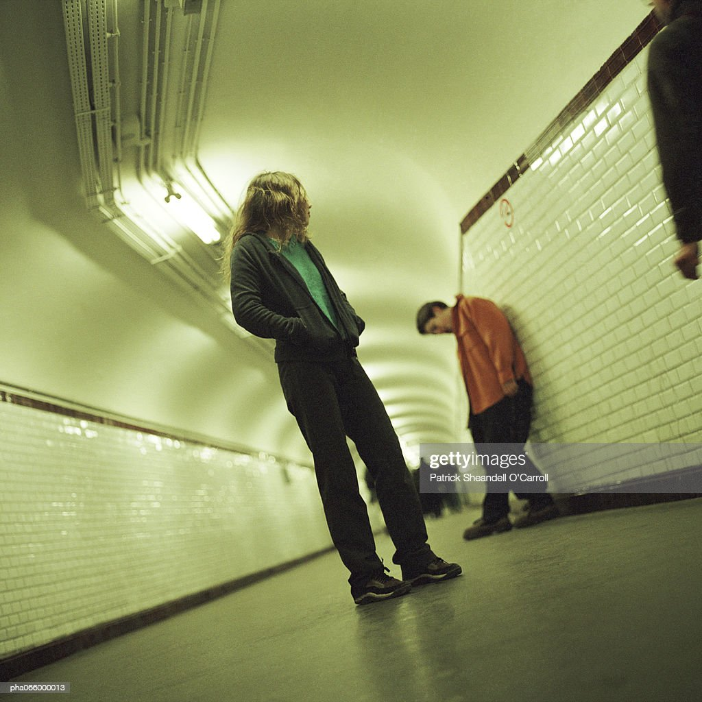 Young people standing in subway corridor : Stockfoto
