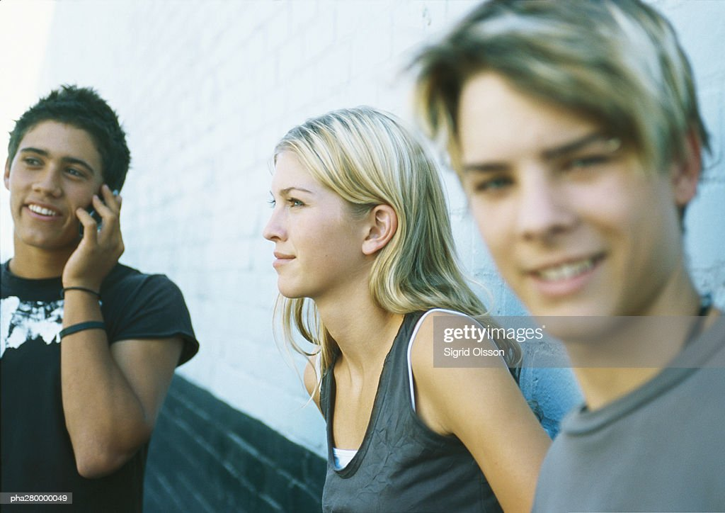 Young people standing next to wall, one using cell phone : Stockfoto