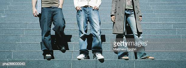Young people standing on steps, waist down