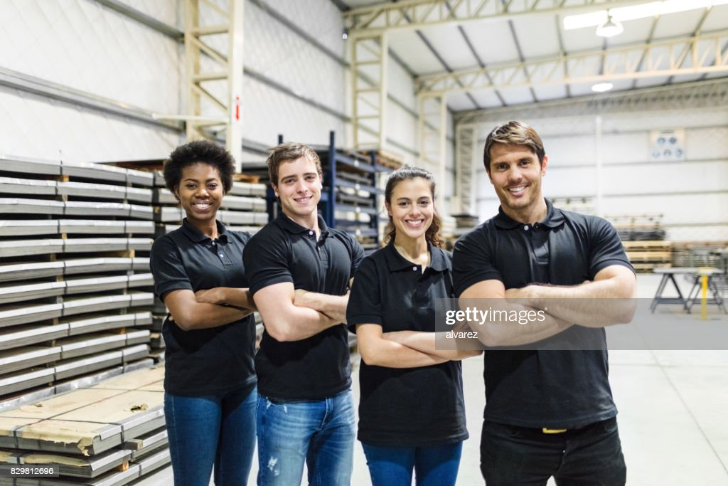 Young people standing together in factory : Foto de stock
