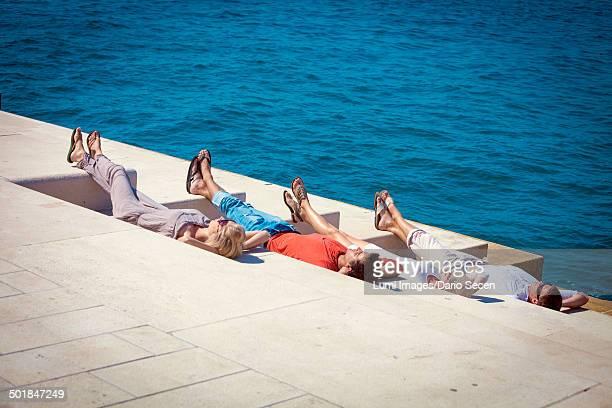 Young people sunbathing on pier, listening to music, Zadar, Croatia