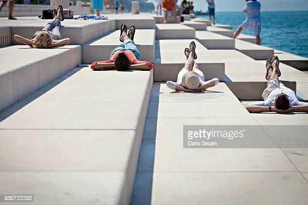 Young people sunbathing on pier, listening to Sea Organ, Zadar, Croatia