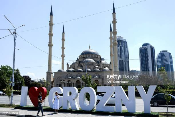 Young people take a photo in front of the Heart of Chechnya Akhmad Kadyrov Mosque and large letters reading 'I love Grozny' in central Grozny on July...