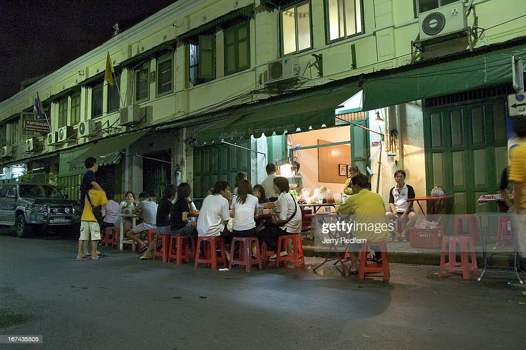 Young people take in a late-night snack at a street-side restaurant in the Rattanakosin area of Bangkok..